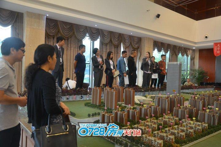 活动还没有开始,有的来宾正在听置业顾问讲解沙盘模型