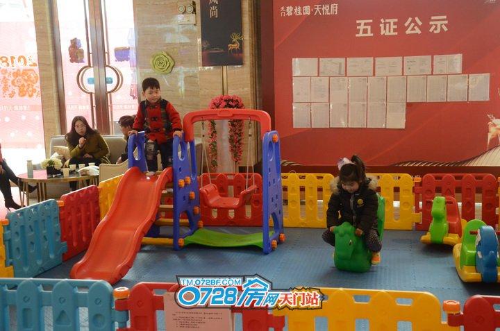 家长在挑选房子,小孩在游乐区玩得不亦乐乎,让家长可以安心选房